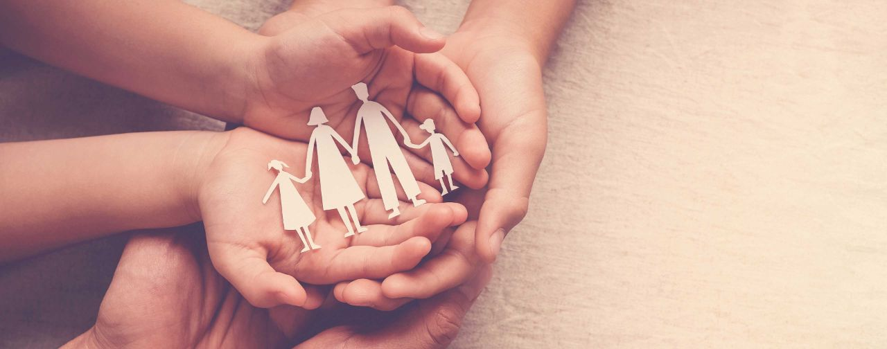A family of husband, wife and child holding hands one on top of the other, with the topmost hand holding a paper cutout of a family