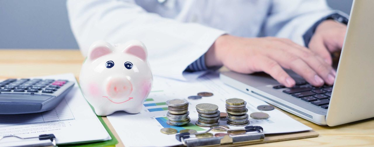 Healthcare profession sitting next a piggy bank