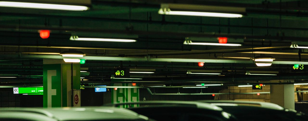 Photo of a parking lot showing the tops of several cars lined up there, with sensors and signboards visible above them