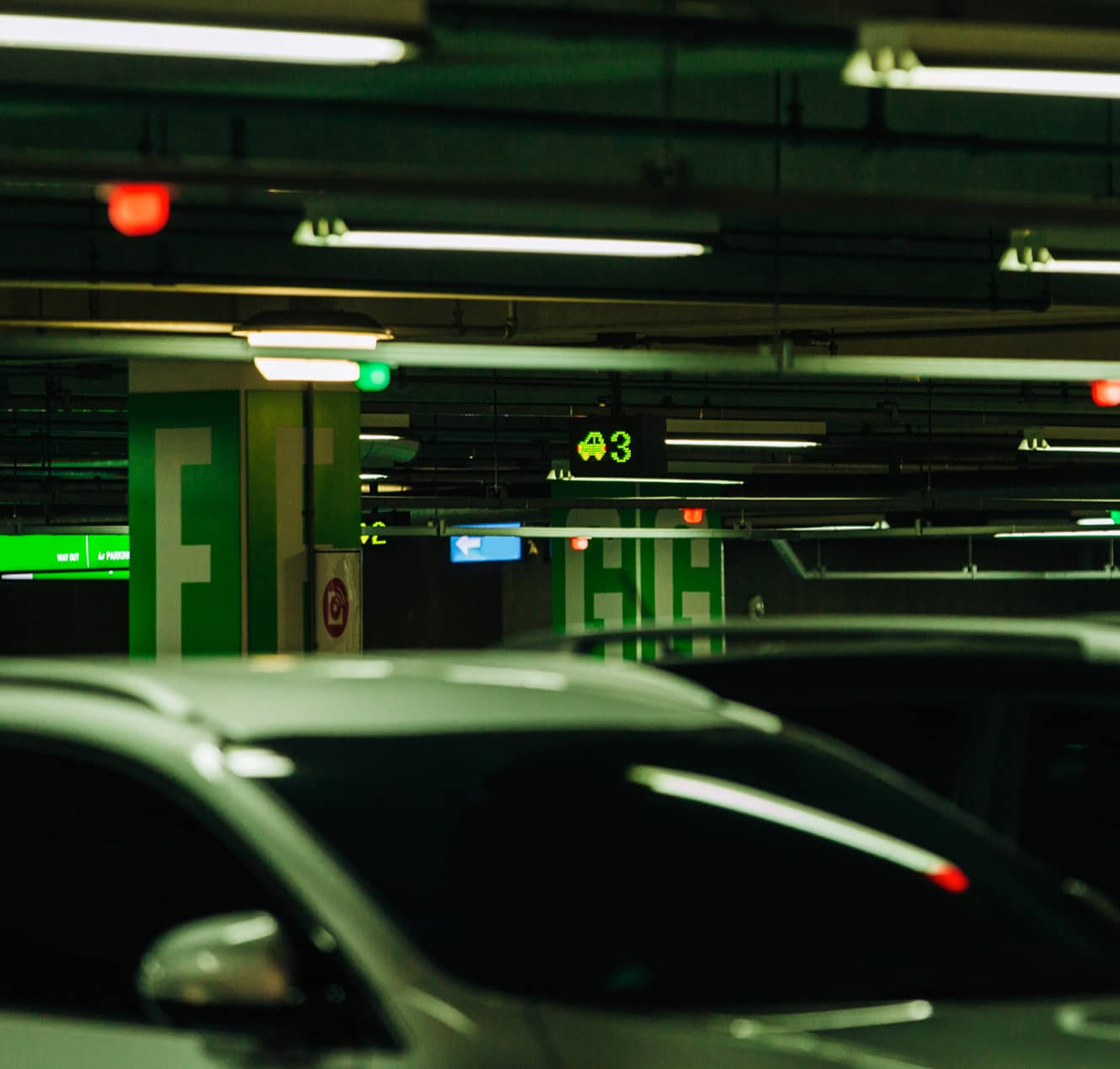 Photo of a parking lot showing the tops of several cars lined up there, with sensors and signboards visible above them.