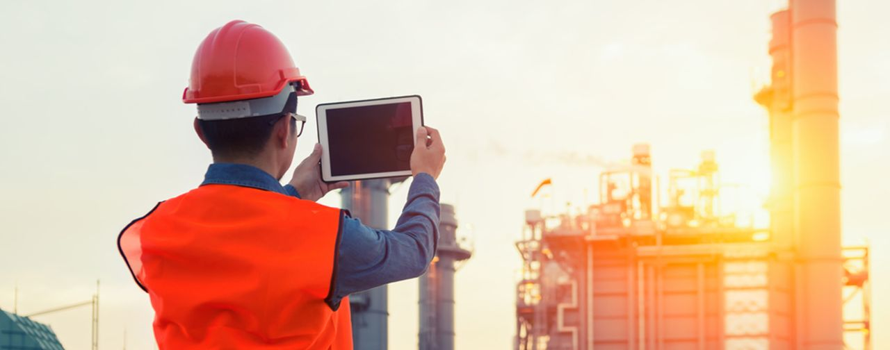 Oil and Gas Worker Holding a Tablet Up Against a Refinery