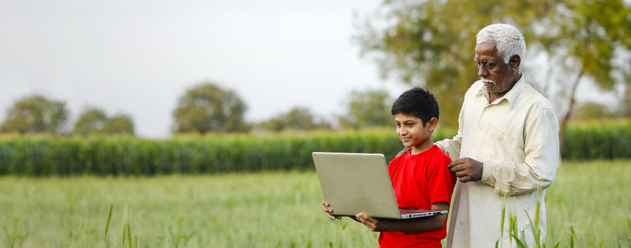 Farmer and grandson in field with laptop