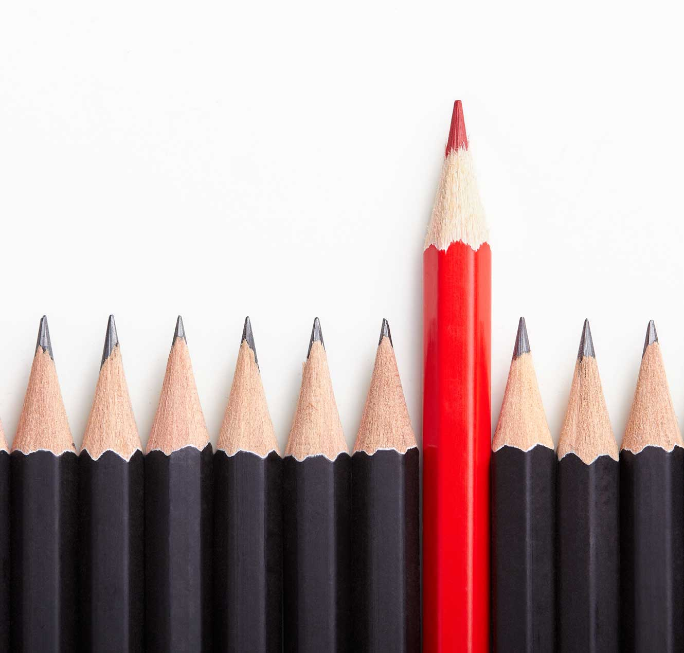Red pencil standing out from a crowd of identical black pencils.