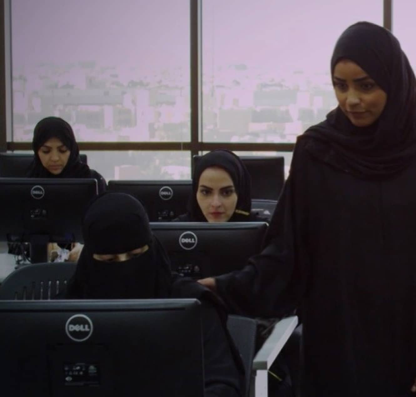 A trainer leads other women, all in headscarves or burqas and sitting in front of computers, during a learning and development session