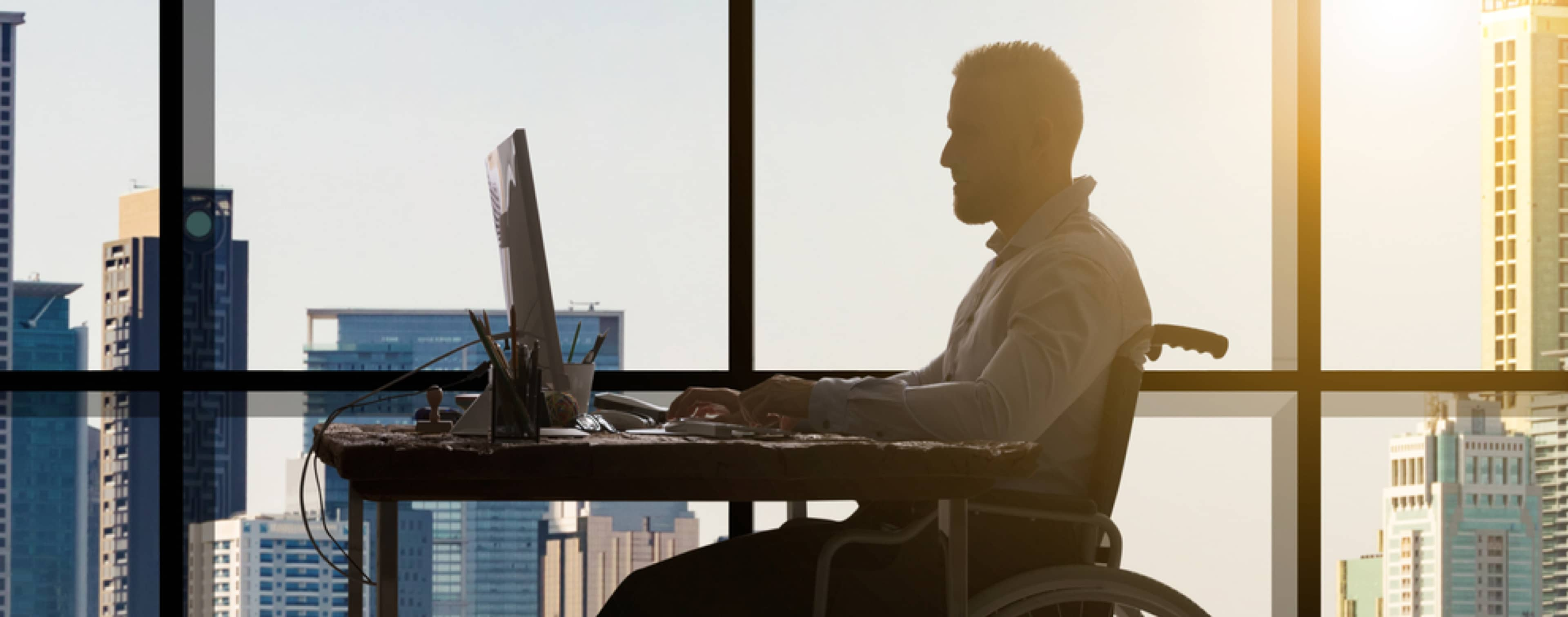 A man in a wheelchair works on his computer, everything silhouetted against the sun