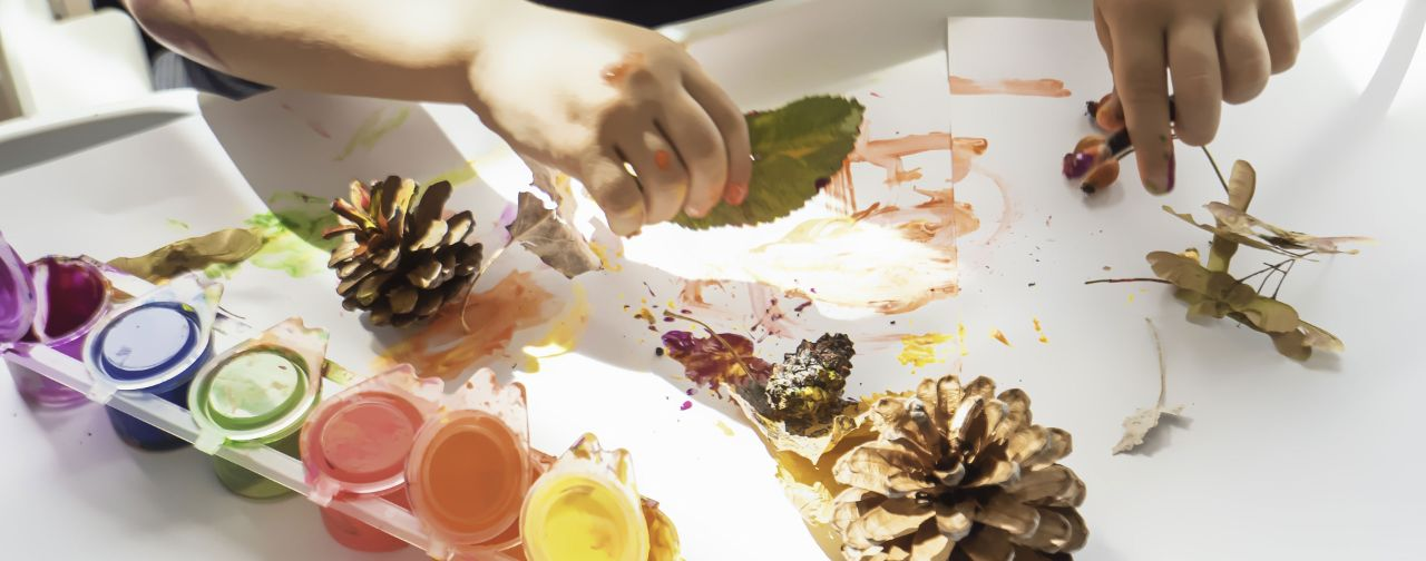 Creating artwork on a paper using paints and leaves