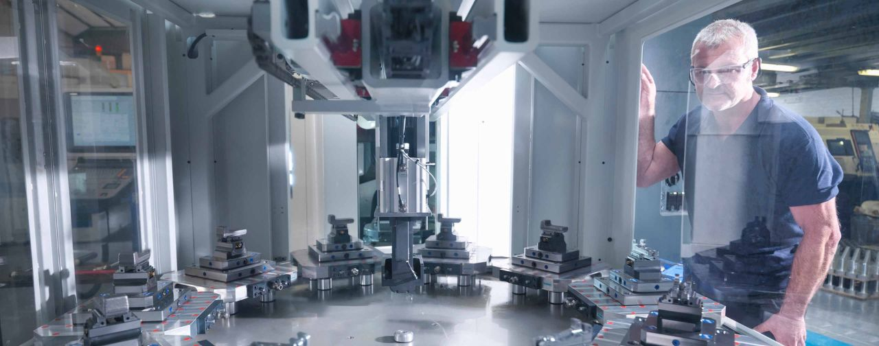 An engineer leverages a digital twin model to inspect automatic lathe in factory