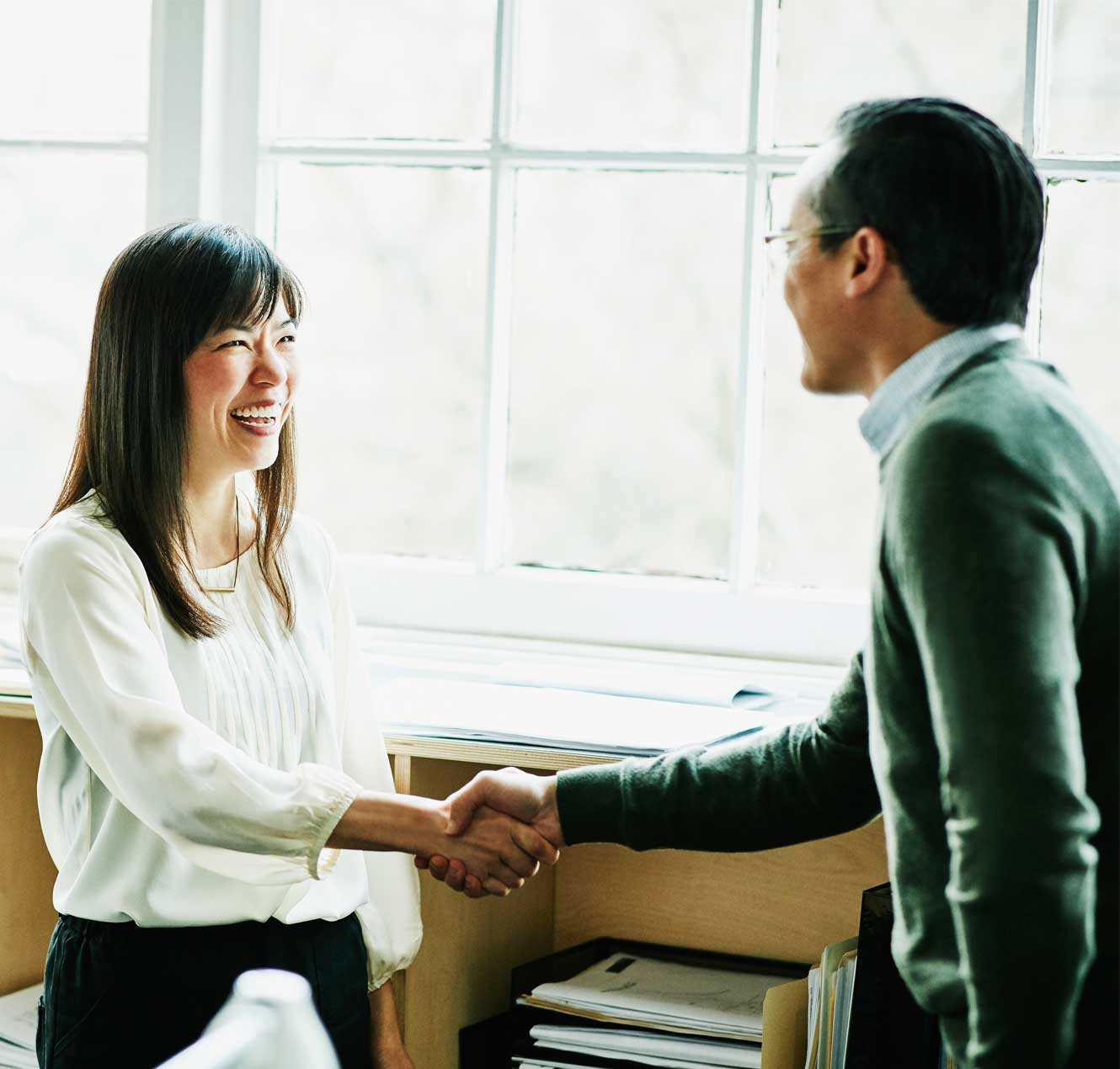 business woman shaking hands with a customer due to positive outcomes and increased customer loyalty enabled by Oracle CX cloud