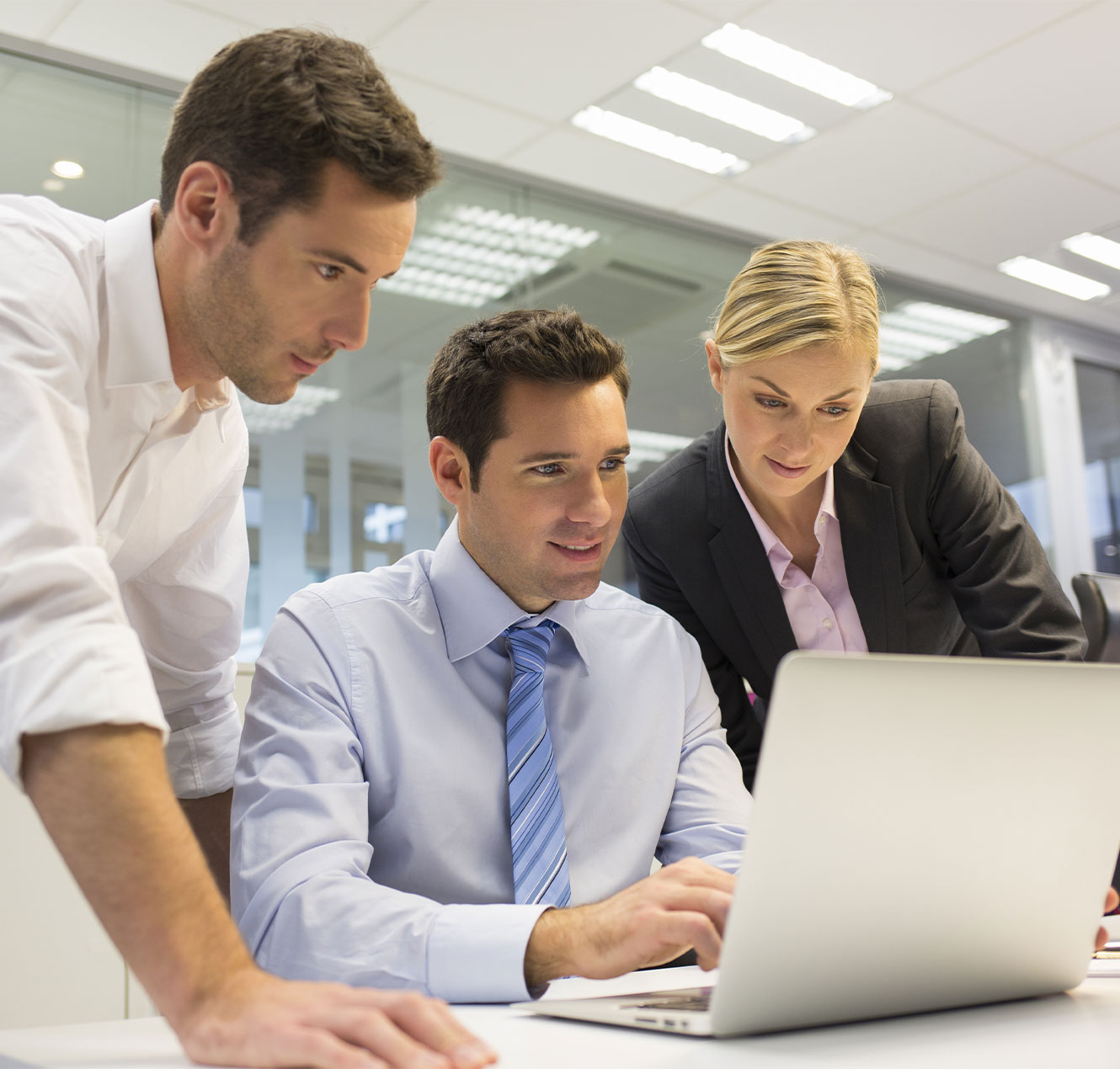 Three colleagues looking at laptop screen