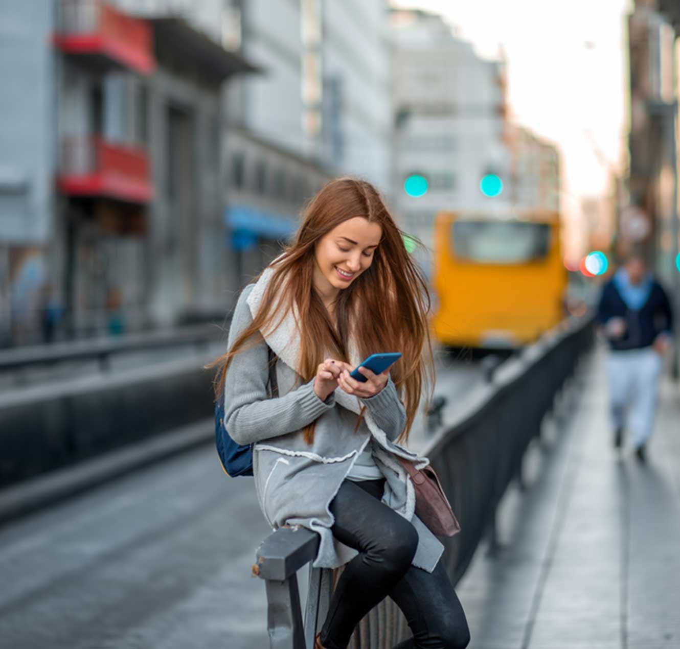 Young Lady Perched on a Railing, Smiling and Looking at Her Phone