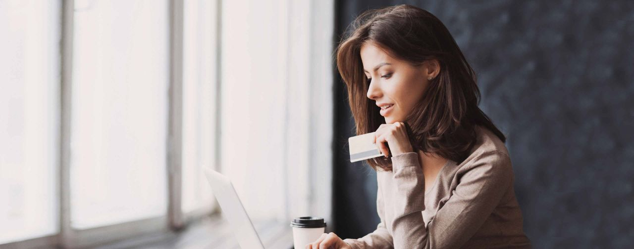 Young woman Holding Credit Card and Using her Laptop